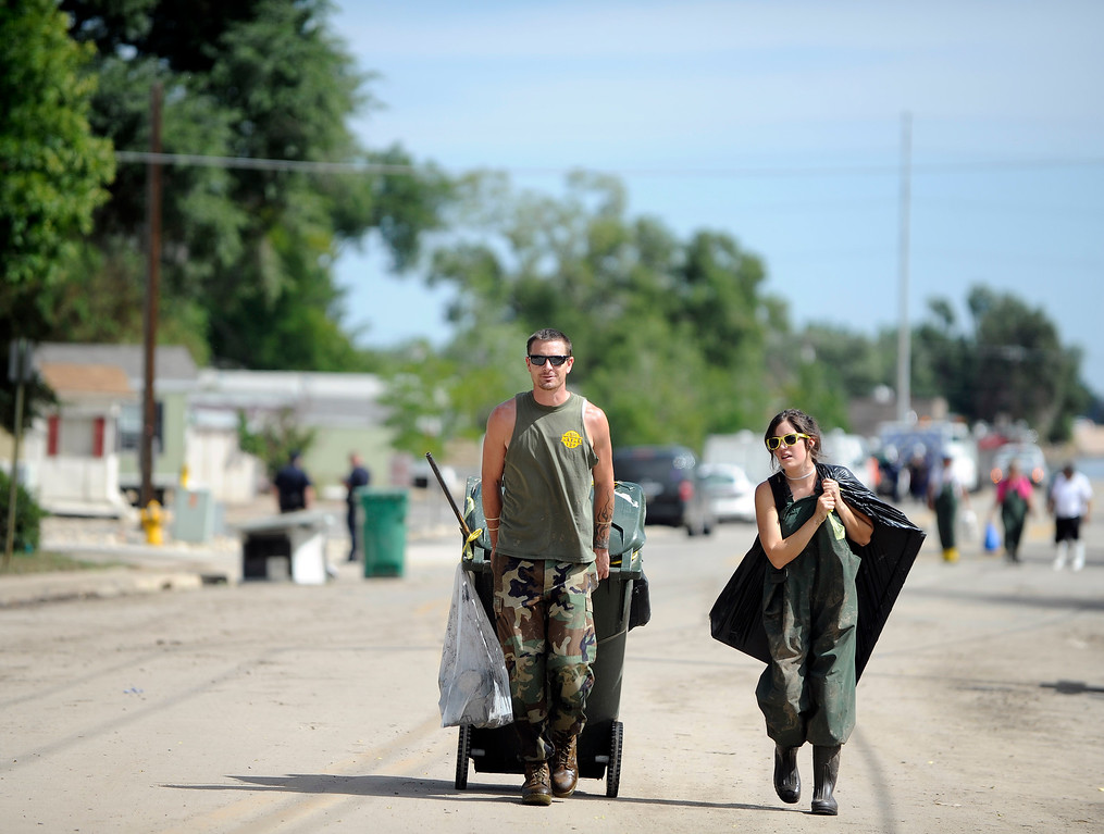 . EVANS, CO - SEPTEMBER 18:  Michael Conklin, left, and girlfriend Shanna Cervantes haul belongings from the flood damaged home of Cervantes\' grandparents in Evans, CO on Wednesday, September 18, 2013. The pair were walking out the the damaged neighborhood on 37th Street. Residents were ordered out of the homes as FEMA surveyed the flood damage. They said the mud and water damaged all the clothing and furniture but they were hoping to be able salvage some photos. (Photo By Cyrus McCrimmon/The Denver Post)