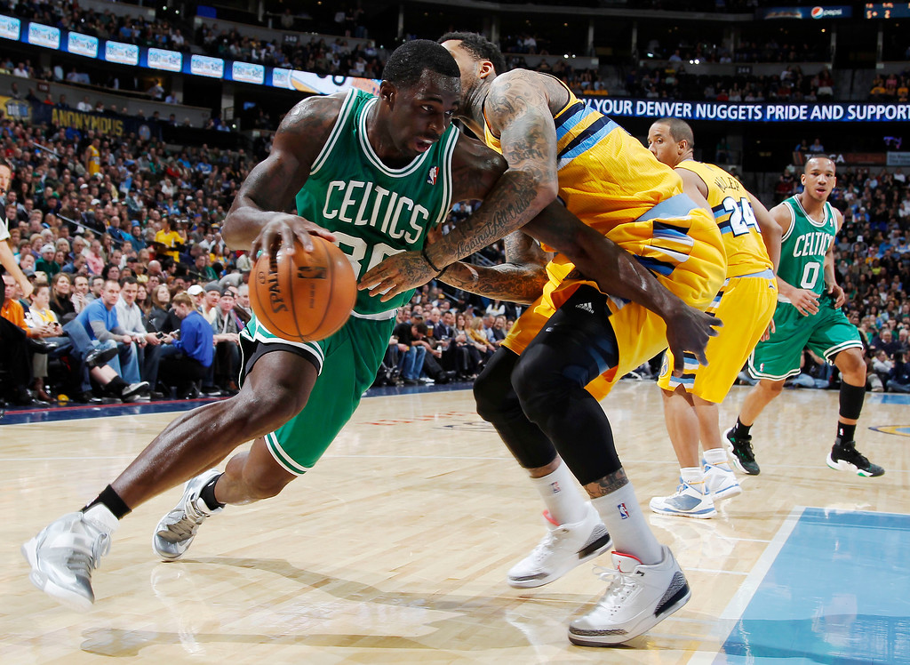 . Boston Celtics forward Brandon Bass works ball inside past Denver Nuggets forward Wilson Chandler during the first quarter of an NBA basketball game in Denver on Tuesday, Feb. 19, 2013. (AP Photo/David Zalubowski)