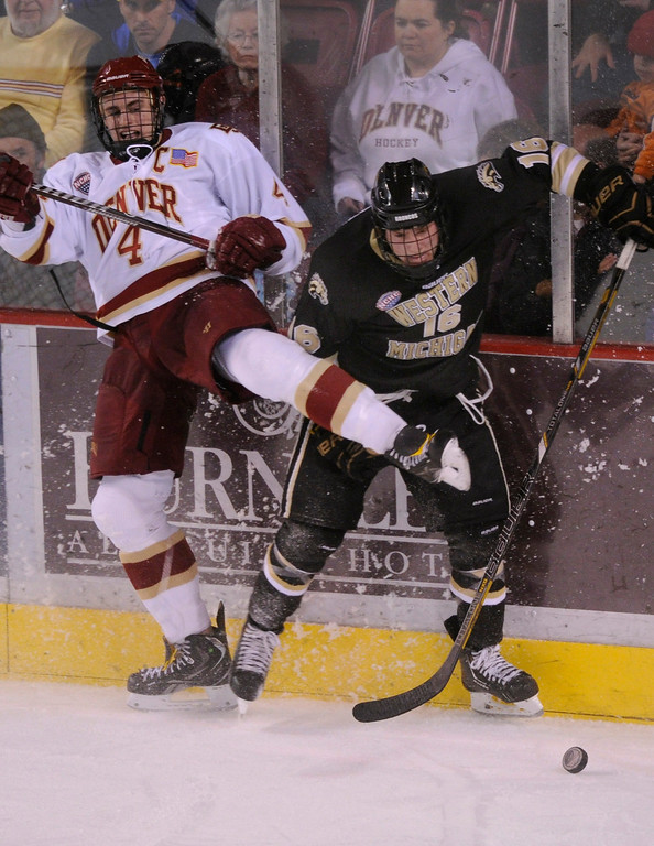 . DENVER, CO. - NOVEMBER 16: Denver defenseman Josiah Didier (4) and Western Michigan wing Nolan LaPorte (16) went for the puck along the boards in the final period. The University of Denver hockey team defeated Western Michigan 1-0 at Magness Arena Saturday night, November 16, 2013.  Photo By Karl Gehring/The Denver Post