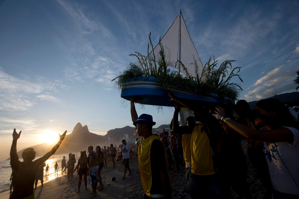 ". Simpatia e Quase Amor or ""Kindness is almost love,\"" block party members faithfully carry a boat filled with flowers as an offering to the sea goddess,Yemanja, during a pre-Carnival celebration in Rio de Janeiro, Brazil, Saturday, Feb. 2, 2013. Worshippers honor the deity, offering flowers and launching boats, large and small, into the ocean showing their gratitude for her blessings bestowed upon them. The belief in the goddess comes from the African Yoruban religion brought to America by West African slaves. (AP Photo/Silvia Izquierdo)"