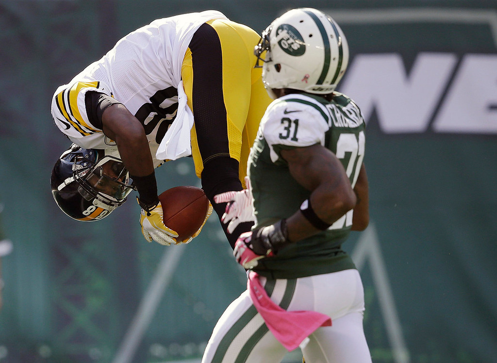. Pittsburgh Steelers\' Emmanuel Sanders (88) flips into the end zone for a touchdown as New York Jets\' Antonio Cromartie (31) chases him during the second half of an NFL football game Sunday, Oct. 13, 2013, in East Rutherford, N.J.  (AP Photo/Seth Wenig)