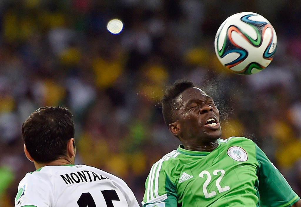 . Iran\'s Pejman Montazeri, left, and Nigeria\'s Kenneth Omeruo battle for the ball during the group F World Cup soccer match between Iran and Nigeria at the Arena da Baixada in Curitiba, Brazil, Monday, June 16, 2014.  (AP Photo/Martin Meissner)