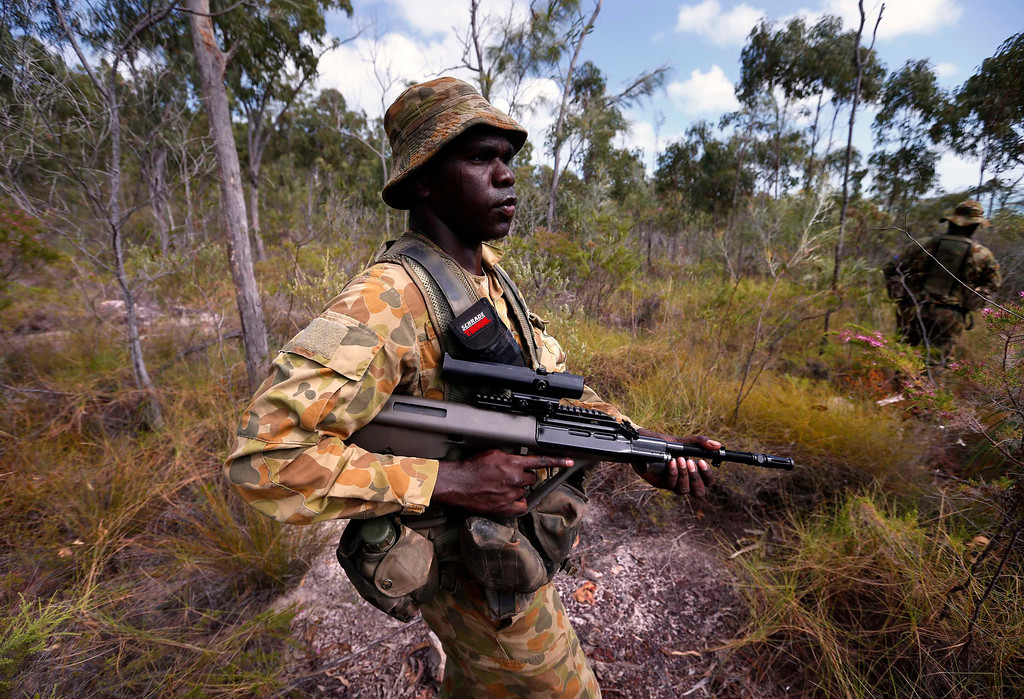 . Lance-corporal Vinnie Rami, an indigenous soldier from Australia\'s North West Mobile Force (NORFORCE) unit, holds his F88 Austeyr rifle as he walks through thick bushland during a surveillance and reconnaissance patrol around Astell Island, part of the English Company Islands, located inside Arnhem Land in the Northern Territory July 17, 2013. NORFORCE is a surveillance unit that employs ancient Aboriginal skills to help in the seemingly impossible task of patrolling the country\'s vast northwest coast. NORFORCE\'s area of operations is about 1.8 million square km (700,000 square miles), covering the Northern Territory and the north of Western Australia. Aboriginal reservists make up a large proportion of the 600-strong unit, and bring to bear their knowledge of the land and the food it can provide. Fish, shellfish, turtle eggs and even insects supplement rations during the patrol, which is on the lookout for illegal foreign fishing vessels and drug smugglers, as well as people smugglers from neighboring Indonesia. Picture taken July 17, 2013. REUTERS/David Gray