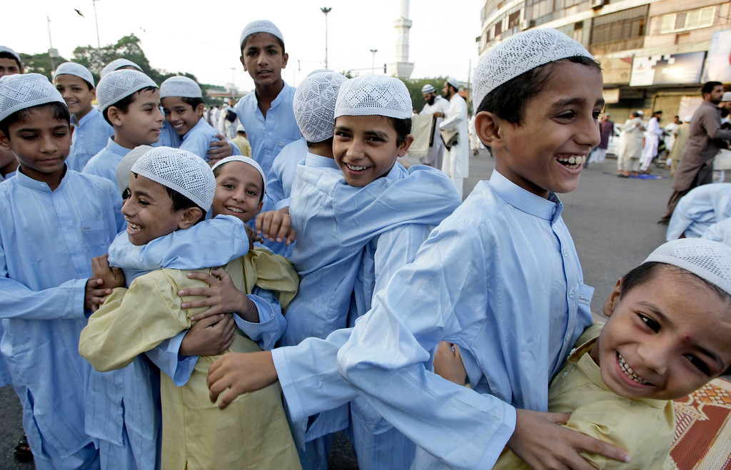 """. Pakistani boys greet each other after praying on the first day of the Muslim holiday of Eid al-Adha, or \""""Feast of Sacrifice\"""", in Karachi, Pakistan, Wednesday, Oct. 16, 2013.   (AP Photo/Fareed Khan)"""