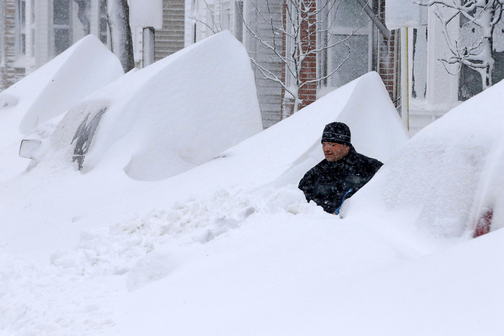 . John Silver shovels snow between buried cars in front of his home on Third Street in South Boston, Saturday, Feb. 9, 2013. (AP Photo/Gene J. Puskar)