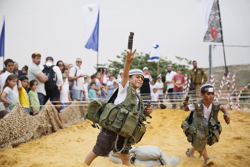 . An Israeli boy dresses wearing a military vest  throws a mock granade during a traditional military weapon display to mark the 66th anniversary of Israel\'s Independence at the West Bank settlement of Efrat on May 6, 2014 near the biblical city of Bethlehem. Israelis are marking Independence Day, celebrating the 66th year since the founding of the Jewish State in 1948 according to the Jewish calendar. AFP PHOTO/GALI TIBBON