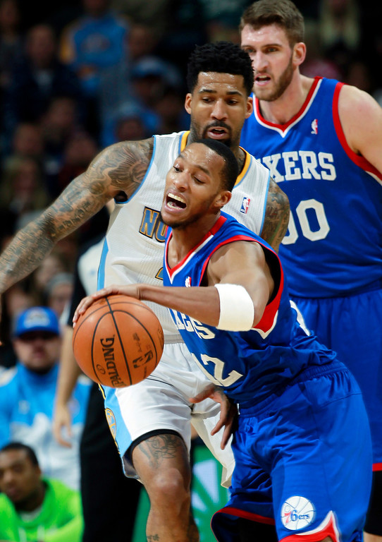 . Philadelphia 76ers guard Evan Turner, front, reaches out to corral a loose ball as Denver Nuggets forward Wilson Chandler, center, covers and 76ers center Spencer Hawes stand near in the third quarter of the Sixers\' 114-102 victory in an NBA basketball game in Denver on Wednesday, Jan. 1, 2014. (AP Photo/David Zalubowski)