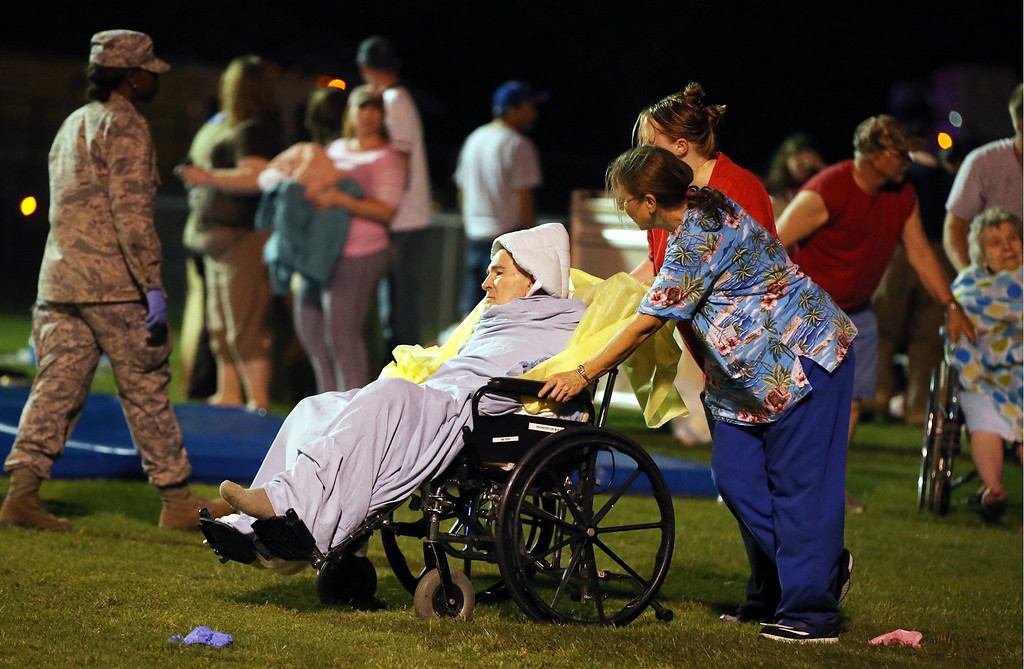 . Emergency workers assist an elderly person at a staging area at a local school stadium Wednesday, April 17, 2013, in West, Texas. An explosion Wednesday night at a fertilizer plant near Waco sent flames shooting high into the night sky, leaving the factory a smoldering ruin, causing major damage at nearby buildings and injuring numerous people. (AP Photo/Waco Tribune Herald, Rod Aydelotte)