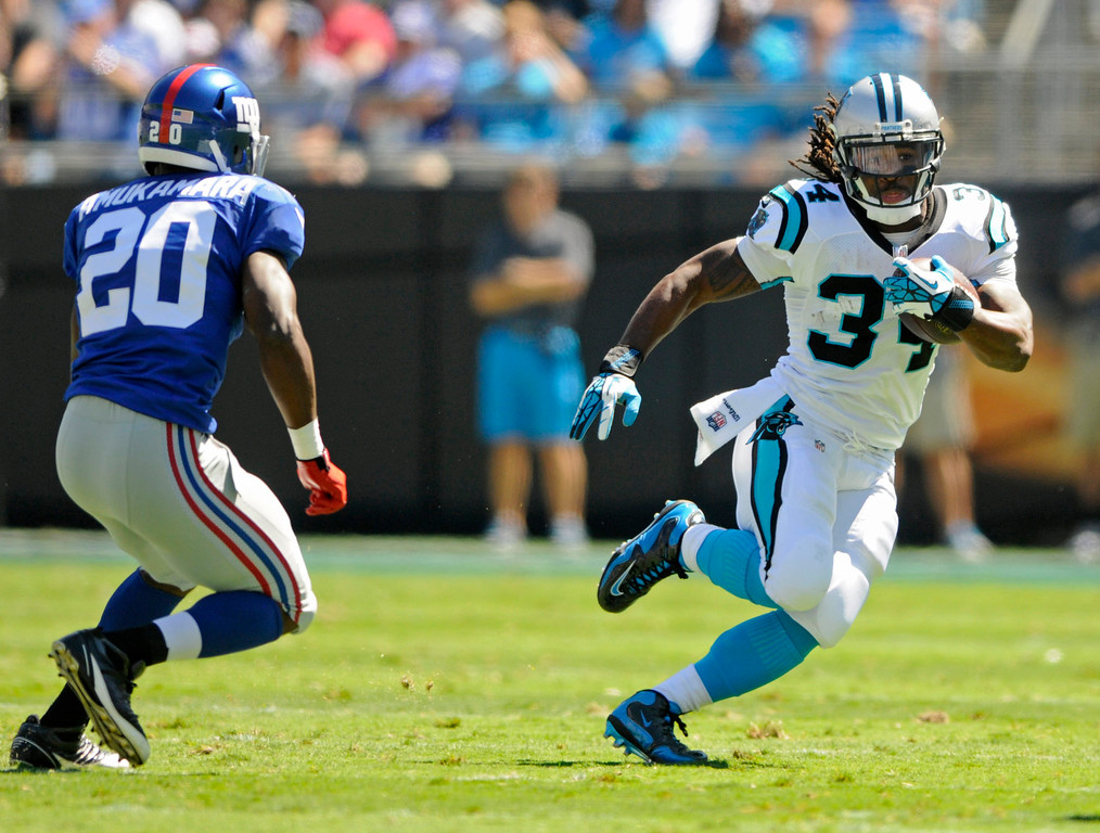. Carolina Panthers running back DeAngelo Williams (34) tries to run past New York Giants cornerback Prince Amukamara (20) during the first half of an NFL football game in Charlotte, N.C., Sunday, Sept. 22, 2013. (AP Photo/Mike McCarn)