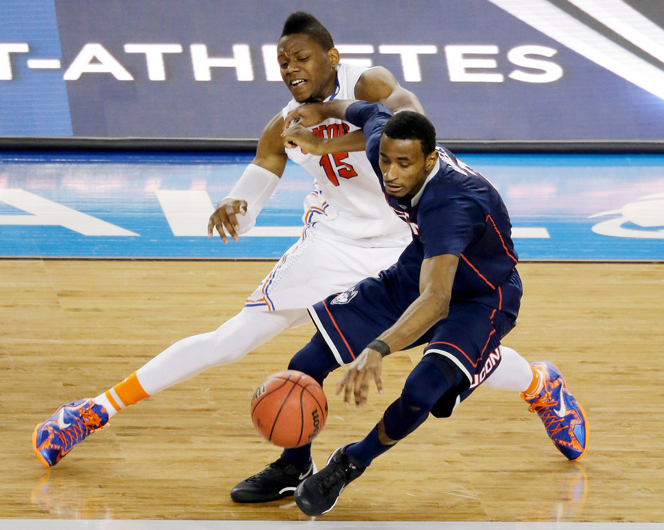 . Connecticut forward DeAndre Daniels works to maintain control of the ball as Florida forward Will Yeguete (15) defends during the second half of the NCAA Final Four tournament college basketball semifinal game Saturday, April 5, 2014, in Arlington, Texas. (AP Photo/Tony Gutierrez)