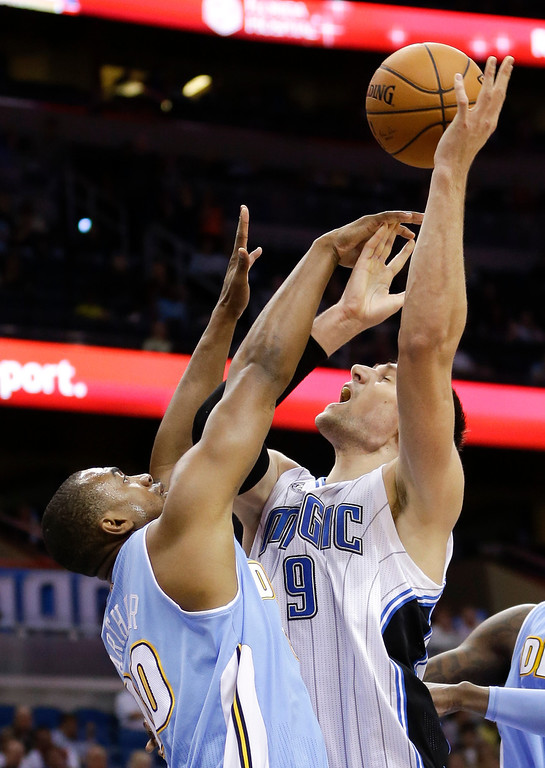 . Orlando Magic\'s Nikola Vucevic (9) manages to get off a shot over Denver Nuggets\'s Darrell Arthur, left, during the second half of an NBA basketball game in Orlando, Fla., Wednesday, March 12, 2014. Denver won 120-112. (AP Photo/John Raoux)