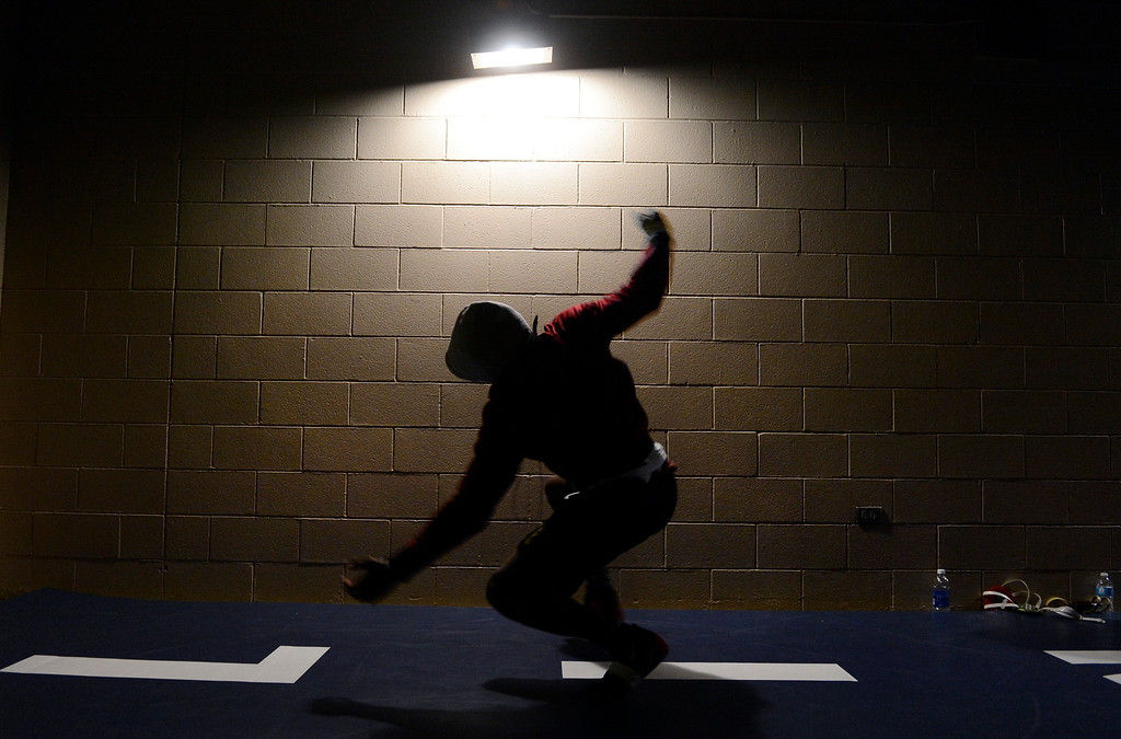 . DENVER, CO. - FEBRUARY 22ND: Corry Williams, Ponderosa High School, center, warms-up on a practice mat before wrestling Geoffrey Curtis, Pine Creek High School, in the 5A 182lb quarterfinal match at the  Colorado State Wrestling Championships at the Pepsi Center in Denver, Colorado, February 22nd, 2013. (Photo By Andy Cross / The Denver Post)