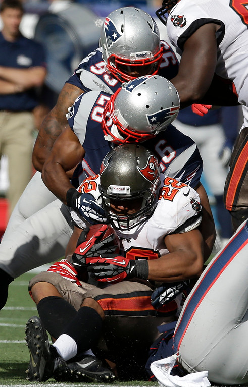 . New England Patriots defensive end Michael Buchanan (99) and defensive back Logan Ryan (26) tackle Tampa Bay Buccaneers running back Doug Martin (22) in the second half of an NFL football game Sunday, Sept. 22, 2013, in Foxborough, Mass. (AP Photo/Stephan Savoia)