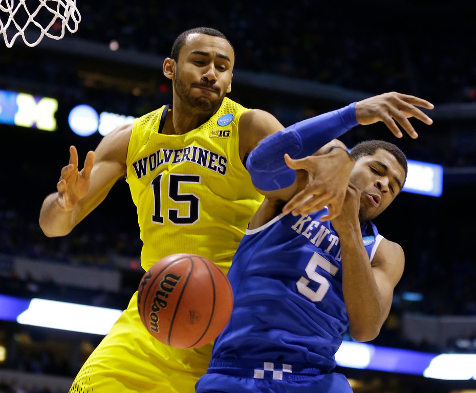 . Michigan\'s Jon Horford (15) and Kentucky\'s Andrew Harrison battle for a loose ball during the second half of an NCAA Midwest Regional final college basketball tournament game Sunday, March 30, 2014, in Indianapolis. (AP Photo/Michael Conroy)