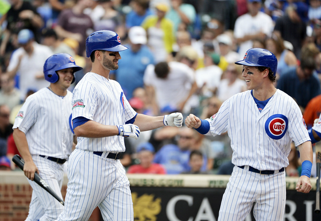. Chris Coghlan #8 of the Chicago Cubs (R) fist bumps teammate Justin Ruggiano #20 after Coghlan scored on a sacrifice fly hit by Ruggiano during the sixth inning against the Colorado Rockies at Wrigley Field on July 31, 2014 in Chicago, Illinois.  (Photo by Brian Kersey/Getty Images)