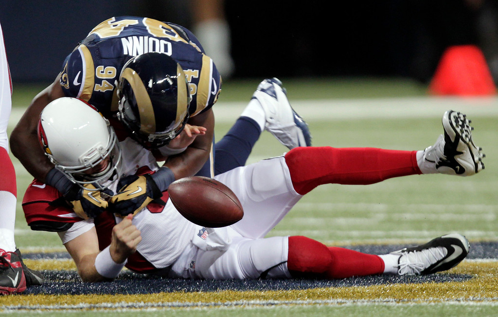 . Arizona Cardinals quarterback Carson Palmer, bottom, fumbles the ball as he is sacked for a 7-yard loss by St. Louis Rams defensive end Robert Quinn during the first quarter of an NFL football game, Sunday, Sept. 8, 2013, in St. Louis. The Cardinals recovered the fumble. (AP Photo/Tom Gannam)
