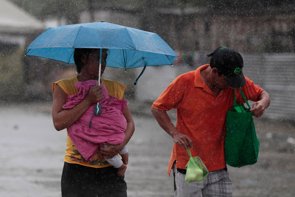 . A Filipino woman holds a baby during a brief rainfall in Manila, Philippines on Monday, Aug. 12, 2013. Powerful Typhoon Utor battered the northern Philippines on Monday, toppling power lines and dumping heavy rains across mountains, cities and food-growing plain. The storm killed at least one man in a landslide and left 45 fishermen missing.   (AP Photo/Aaron Favila)