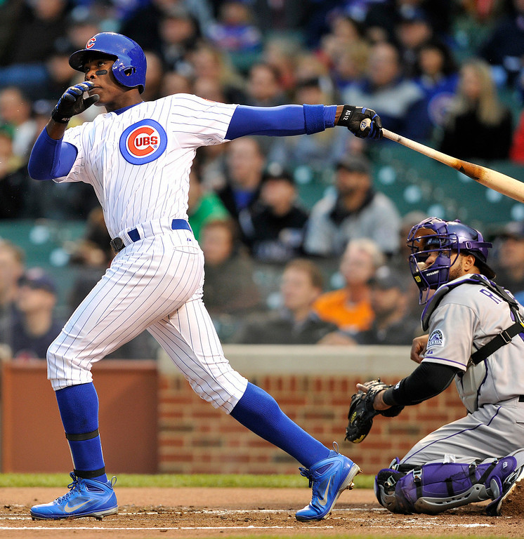 . Chicago Cubs\' Alfonso Soriano watches his two-run home run as the Colorado Rockies\' Wilin Rosario looks on during the first inning of a baseball game Monday, May 13, 2013, in Chicago. (AP Photo/Jim Prisching)