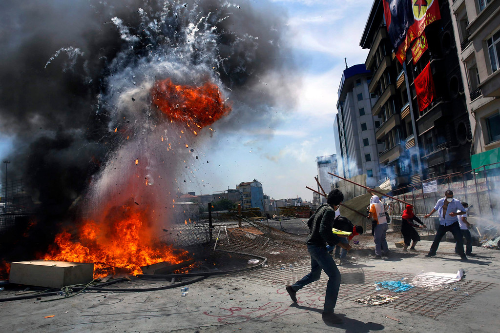 . Protesters react after an explosion on a barricade during clashes in Istanbul\'s Taksim square June 11, 2013. REUTERS/Yannis Behrakis
