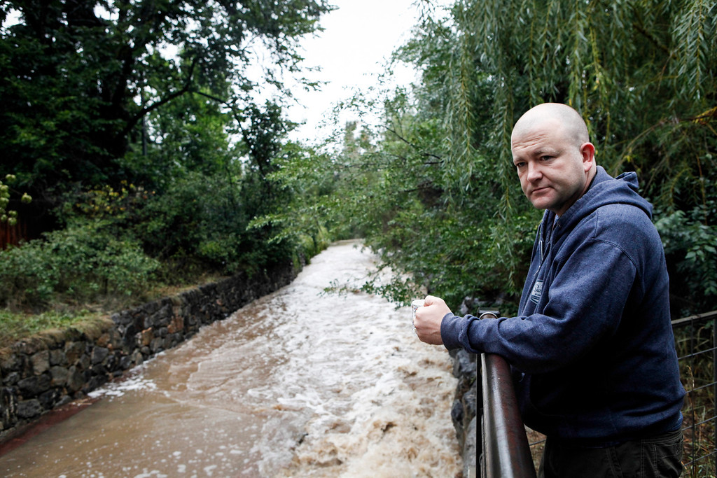 . BOULDER, COLORADO - SEPTEMBER 12: Kieran O\'Kane has his morning coffee behind his home along the Bear Creek Path, which flooded early today after three days of heavy rainfall September 12, 2013 in Boulder, Colorado. An estimated 6-10 inches of rain fell in 12-18 hours and more is expected throughout the day. Flash flood sirens warned people to stay away from Boulder Creek and seek higher ground.  (Photo by Dana Romanoff/Getty Images)