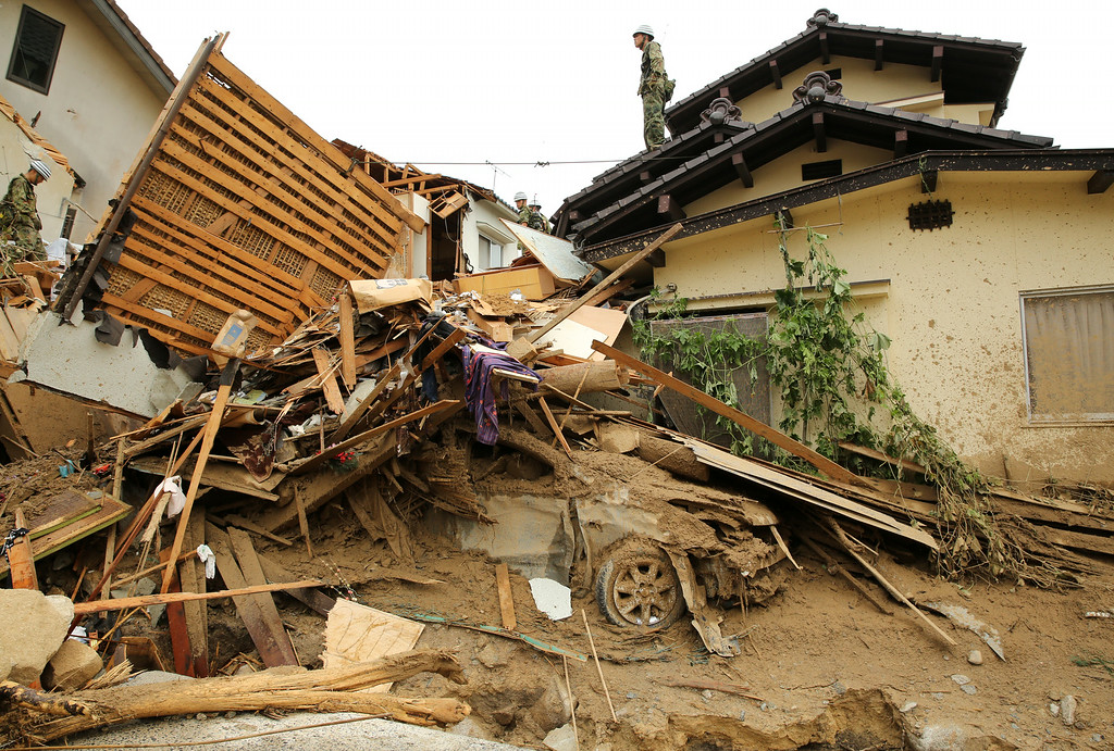. Members of Ground Self-Defense continue the search for missing people among the debris of houses destroyed by a landslide caused by torrential rain at the site of a landslide in a residential area on August 20, 2014 in Hiroshima, Japan.  (Photo by Buddhika Weerasinghe/Getty Images)
