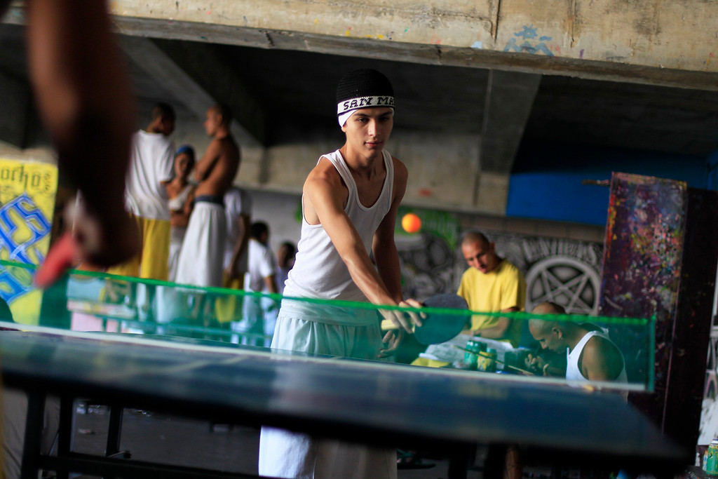 . Jailed gang members play a game of table tennis at the maximum security jail of Izalco in Sonsonate March 5, 2013. Jailed members of the country\'s two most powerful gangs MS-13 and the 18th Street gang (Mara 18), members of civic organizations and Bishop Fabio Colindres celebrated mass to mark the first anniversary since the two gangs signed a truce in March 2012 in an effort to reduce violent crimes in the country.      REUTERS/Ulises Rodriguez