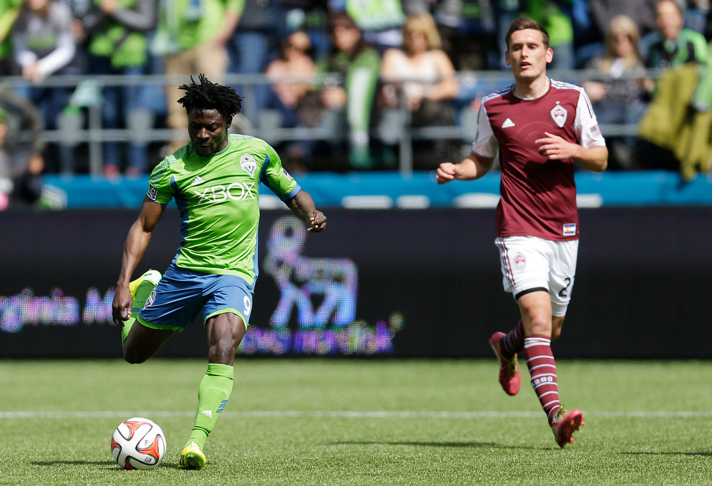 . Seattle Sounders\' Obafemi Martins, left, kicks a goal as Colorado Rapids defender Shane O\'Neill looks on at right, Saturday, April 26, 2014 in the second half of an MLS soccer match in Seattle. The Sounders defeated the Rapids 4-1. (AP Photo/Ted S. Warren)
