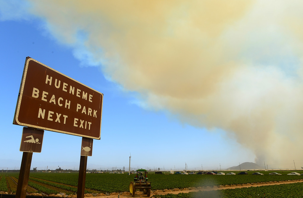 . Farmers drive their tractors on farmland off the Pacific Coast Highway south of Oxnard as smoke rising into the sky and fanned by strong winds ravage hillsides and canyons in nearby Ventura County, northwest of Los Angeles on May 2, 2013.  AFP PHOTO/Frederic J.  BROWN/AFP/Getty Images