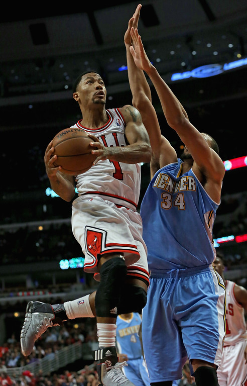 . Derrick Rose #1 of the Chicago Bulls goes up for a shot against JaVale McGee #34 of the Denver Nuggets during a preseason game at the United Center on October 25, 2013 in Chicago, Illinois. The Bulls defeated the Nuggets 94-89.  (Photo by Jonathan Daniel/Getty Images)