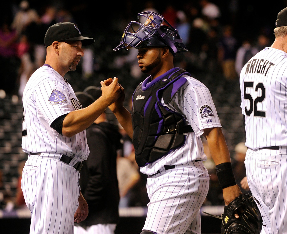 . DENVER, CO. - AUGUST 09: Colorado manager Walt Weiss congratulated catcher Wilin Rosario following the game. The Colorado Rockies defeated the Pittsburgh Pirates 10-1 Friday night, August 9, 2013. Photo By Karl Gehring/The Denver Post