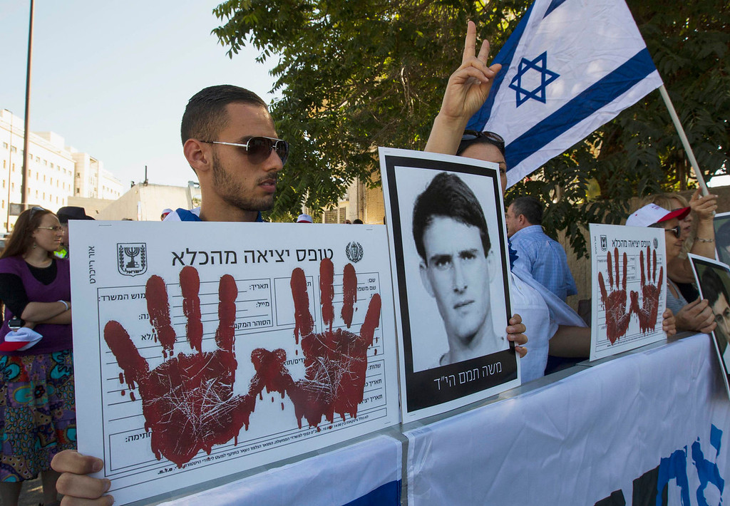 . An Israeli holds a picture of a victim of a militant attack during a protest outside the office of Israel\'s Prime Minister Benjamin Netanyahu in Jerusalem, against the release of Arab prisoners as a step to renew stalled peace talks with the Palestinians, July 28, 2013. Netanyahu on Sunday urged divided rightists in his cabinet to approve the release of 104 Arab prisoners in order to restart peace talk with the Palestinians.   REUTERS/Ronen Zvulun