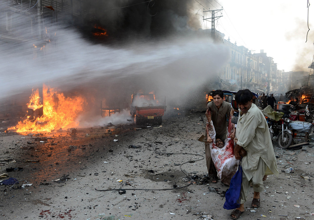 . Pakistani men carry an injured blast victim at the site of a bomb explosion in the busy Kissa Khwani market in Peshawar on September 29, 2013.  AFP PHOTO / HASHAM AHMED/AFP/Getty Images