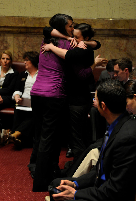 . DENVER, CO. - MARCH 8: Kimberly Weeks, left, hugged friends Katherine Whitney and Elisa Dahlberg after Senator Rollie Heath (D-Boulder) laid over his own bill concerning concealed weapons on college campuses. Weeks is a student at the University of Northern Colorado and testified against the bill earlier this week. The Colorado Senate continued to debate various gun control measures Friday night, March 8, 2013. (Photo By Karl Gehring/The Denver Post)