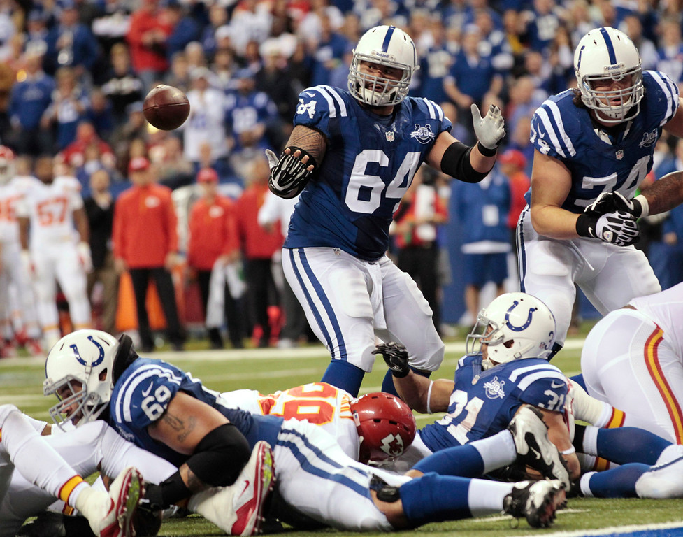 . Indianapolis Colts\' Donald Brown (31) fumbles before the Colts\' Andrew Luck (12) recovered the football and went in for a five-yard touchdown during the second half of an NFL wild-card playoff football game Saturday, Jan. 4, 2014, in Indianapolis. (AP Photo/AJ Mast)