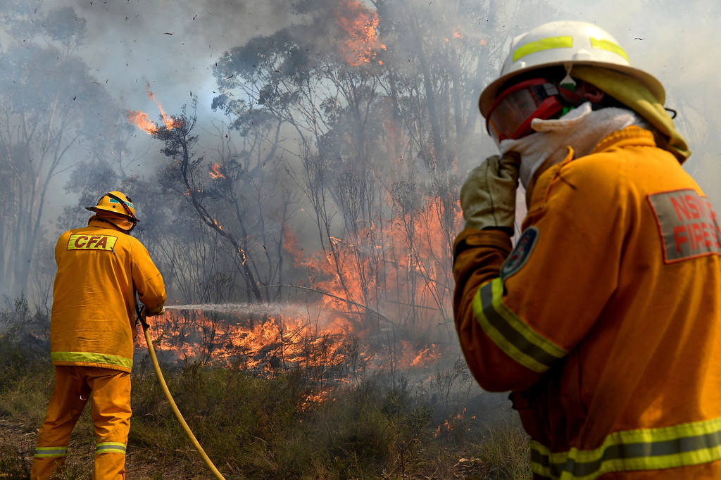 . Firefighters work on putting in containment lines to help control a wildfire near the township of Bell, Australia, Monday, Oct. 21, 2013.  (AP Photo/AAP Image, Dan Himbrechts)