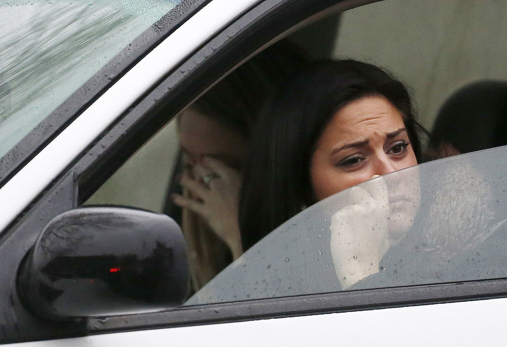 . Women react while waiting in a vehicle to drive away from St. Rose of Lima Roman Catholic Church as officials respond to a bomb threat, Sunday, Dec. 16, 2012, in Newtown, Conn. Worshippers hurriedly left the church Sunday, not far from where a gunman opened fire Friday inside the Sandy Hook Elementary School in Newtown. (AP Photo/Julio Cortez)