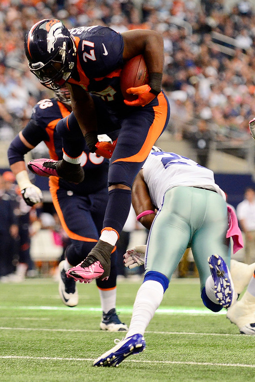 . Knowshon Moreno (27) of the Denver Broncos leaps over J.J. Wilcox (27) of the Dallas Cowboys during the first half of action at AT&T Stadium.   (Photo by AAron Ontiveroz/The Denver Post)