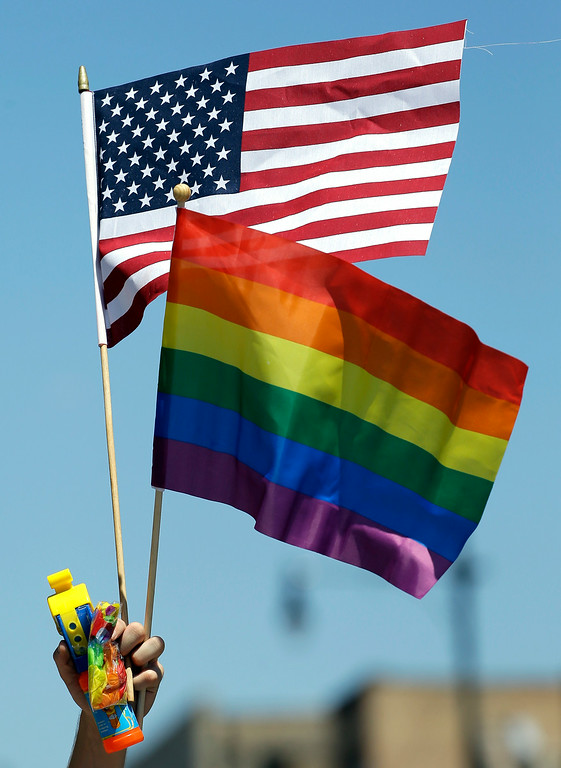 . A participant hold flags at the 45th Annual Chicago Pride Parade during the parade on Broadway Street in Chicago, Sunday, June 29, 2014. The event, the first since Illinois\' law allowing same-sex marriage went into effect, has 200 registered entrants, with about 1 million expected to participate. (AP Photo/Nam Y. Huh)
