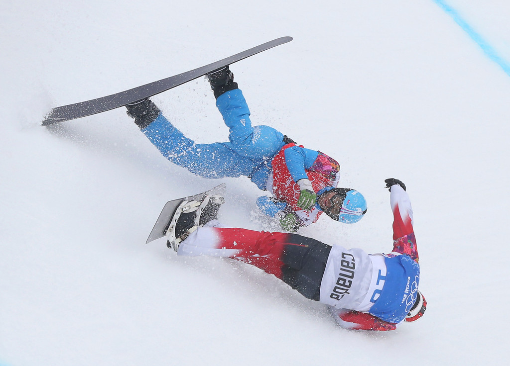 . Austria\'s Markus Schairer, top, and Canada\'s Robert Fagan crash during a men\'s snowboard cross heat at the Rosa Khutor Extreme Park, at the 2014 Winter Olympics, Tuesday, Feb. 18, 2014, in Krasnaya Polyana, Russia. (AP Photo/Sergei Grits)
