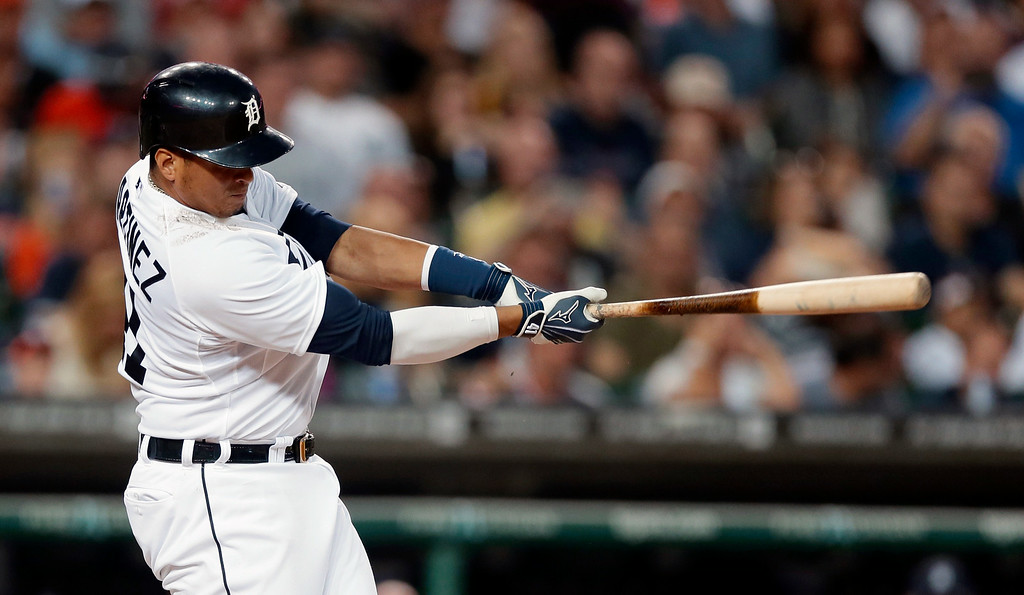 . Detroit Tigers designated hitter Victor Martinez connects for a three-run home run during the fifth inning of an interleague baseball game against the Colorado Rockies, Saturday, Aug. 2, 2014, in Detroit. (AP Photo/Carlos Osorio)