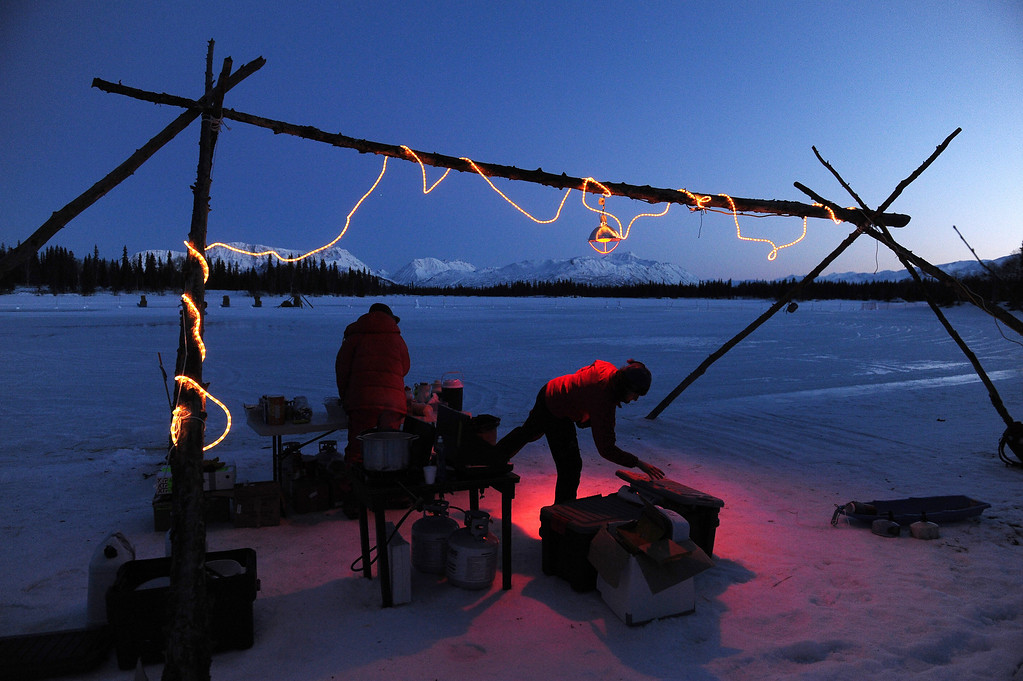 . Iditarod checkers Susanne Rieder and Michelle Keagle work in the cook area as they wait for mushers at the Finger Lake checkpoint during the 2014 Iditarod Trail Sled Dog Race on Sunday evening, March 2, 2014. (AP Photo/The Anchorage Daily News, Bob Hallinen)