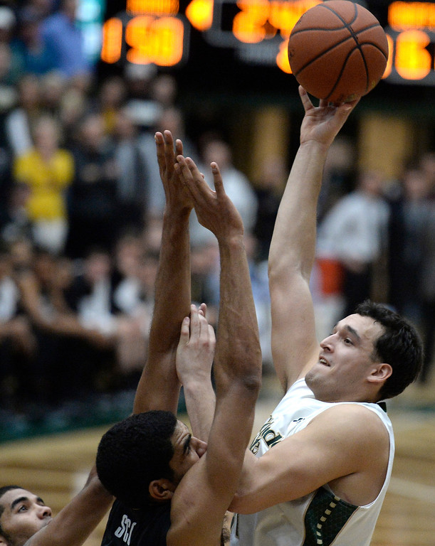 . Colorado State University\'s  J.J. Avila takes a shot over Josh Scott and Xavier Talton during an NCAA game against CU on Tuesday, Dec. 3, 2013, at the Moby Arena in Fort Collins.