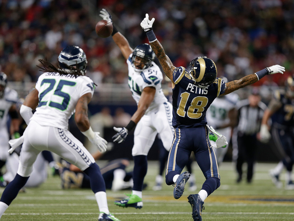 . St. Louis Rams wide receiver Austin Pettis (18) cannot make a catch during the first half of an NFL football game against the Seattle Seahawks, Monday, Oct. 28, 2013, in St. Louis. Seattle Seahawks cornerback Richard Sherman (25) made the interception on the play. (AP Photo/Michael Conroy)