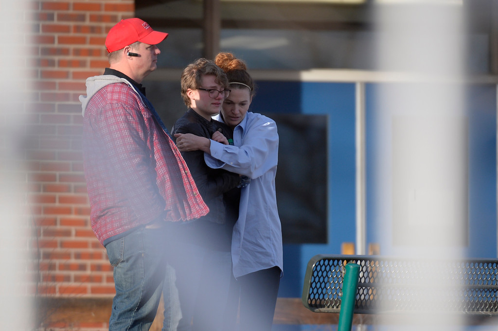 . CENTENNIAL, CO -  A student gets a hug at Euclid Middle School after getting bused their from Arapahoe High School December 13, 2013. A gunman at the school was targeting a teacher at the school. The gunman shot two students in the process and then turned the gun on himself. (Photo by John Leyba/The Denver Post)