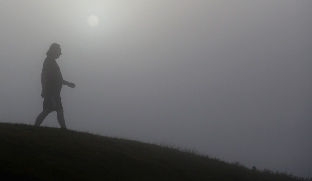 . A visitor to Glastonbury Tor walks past the rising sun as it begins to clear the early morning mist and fog near the town of Glastonbury on September 4, 2013 in Somerset, England. (Photo by Matt Cardy/Getty Images)