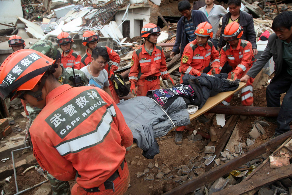 . Rescuers carry a victim\'s body at the quake-hit area on August 4, 2014 in Zhaotong, China. A 6.5-magnitude earthquake hit Zhaotong\'s Ludian county on August 3, killing at least 410 people.  (Photo by ChinaFotoPress/ChinaFotoPress via Getty Images)