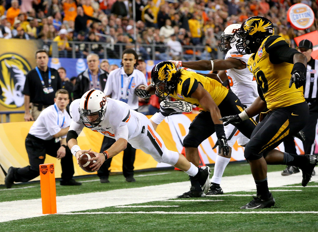 . ARLINGTON, TX - JANUARY 03:  Quarterback Clint Chelf #10 of the Oklahoma State Cowboys dives into the endzone for a 23-yard rushing touchdown in the fourth quarter against the Missouri Tigers during the AT&T Cotton Bowl on January 3, 2014 in Arlington, Texas.  (Photo by Ronald Martinez/Getty Images)