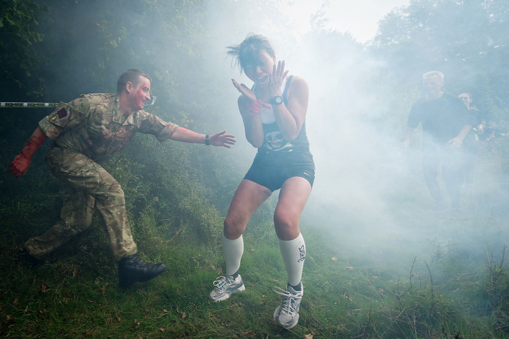 ". A participant is terrified by a ""zombie\"" soldier in a forest section during one of Britain\'s biggest horror events, the \""Zombie Evacuation Race\"" at Carver Barracks near Saffron Walden, England, on October 5, 2013. The race sees thousands of participants attempt to complete a gruelling 5 kilometre cross-country run, while evading \""zombies\"", intent on snatching the three life-line strips hanging from every runner\'s waist.  Those who manage to get through with any strips remaining are named as survivors while those without take home an \""infected\"" badge. LEON NEAL/AFP/Getty Images"