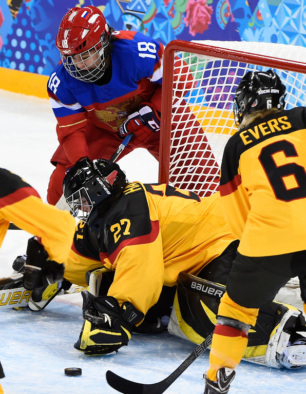 . Germany\'s goalkeeper Viona Harrer saves a shot by Russia\'s Olga Sosina (L) during the Women\'s Ice Hockey Group B match Russia vs Germany at the Shayba Arena during the Sochi Winter Olympics on February 9, 2014. JONATHAN NACKSTRAND/AFP/Getty Images