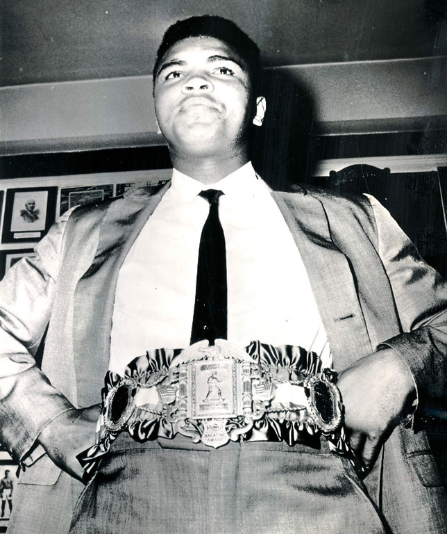 """. Clay Begins Buildup For 2nd Liston Bout NEW YORK, Sept.17--A BELT FOR THE CHAMP--World heavyweight boxing champion Cassius Clay poses wearing the 24-carat gold plated championship belt presented him in New York.  Clay predicted a long reign on the boxing throne for himself and eventual retirement as \""""the undefeated, untarnished and still the prettiest\"""" heavyweight champion of them all.  The belt was presented by Ring Magazine in whose office the ceremony took place. 1964. Credit: AP"""